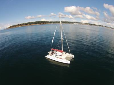 Aerial shot of Fontaine Pajot Athena 38 catamaran anchored in St Aubin's bay Jersey