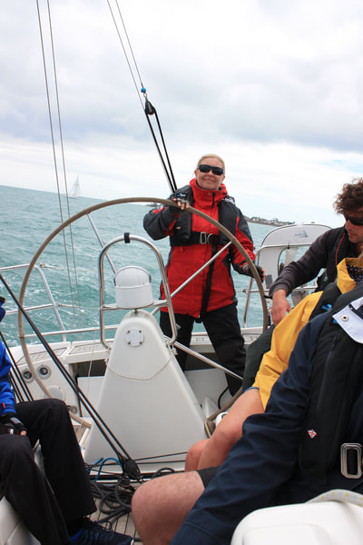 Helming a Dufour 34 Performance on a RYA sailing course in Jersey