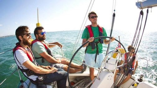 Group enjoying sunshine sailing on a RYA Day Skipper course
